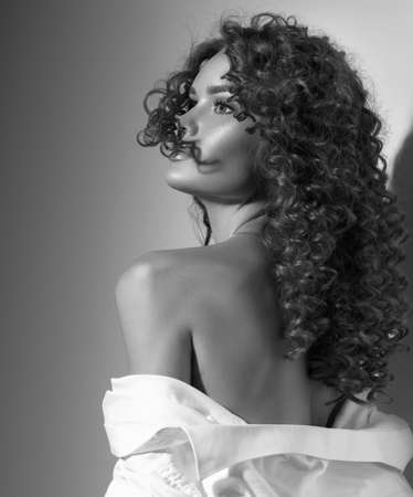 Beautiful young woman with curly hair posing, beauty model portrait, closeup. Beautiful sexy model girl in white cotton shirt. Flying hair, perfect make-up. Hairstyle. Black and white image Banque d'images