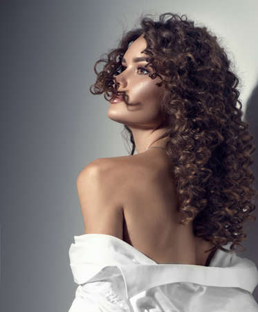 Beautiful young woman with curly hair posing, beauty model portrait, closeup. Beautiful sexy model girl in white cotton shirt. Flying hair, perfect make-up and manicure. Hairstyle. Vertical image Standard-Bild