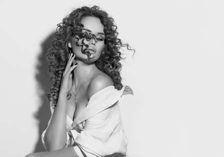Beautiful young woman with curly hair posing, beauty model portrait, closeup. Beautiful sexy model girl in white cotton shirt. Flying hair, perfect make-up and manicure. Hairstyle. Black and white Banque d'images