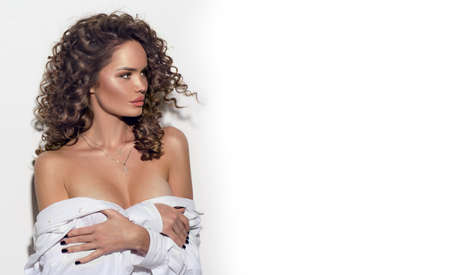 Beautiful young woman with curly hair posing, beauty model portrait, closeup. Beautiful sexy model girl in white cotton shirt. Flying hair, perfect make-up and Hairstyle. Banque d'images