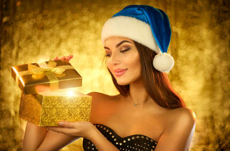 Surprised Christmas Winter Woman opening magic Christmas Gift box and smiling over golden background. Beautiful New Year and Xmas scene, Beauty Fashion Model Girl With Present Box Banque d'images