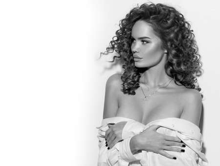 Beautiful young woman with curly hair posing, beauty model portrait, closeup.  Hairstyle. Black and white image
