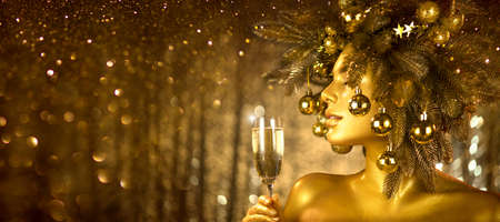 Beauty Golden Christmas Woman with champagne. Beautiful girl drinking sparkling wine, over glowing holiday background. Xmas, New Year celebration.