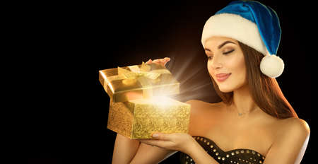 Surprised Christmas Winter Woman opening magic Christmas Gift box and smiling over black background. Beautiful New Year and Xmas scene, Beauty Fashion Model Girl With Present Box Banque d'images