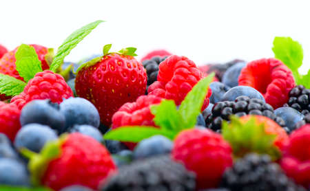 Berries. Various colorful berries background. Mint leaves, Strawberry, Raspberry, Blackberry, Blueberry close-up backdrop, isolated on white Standard-Bild