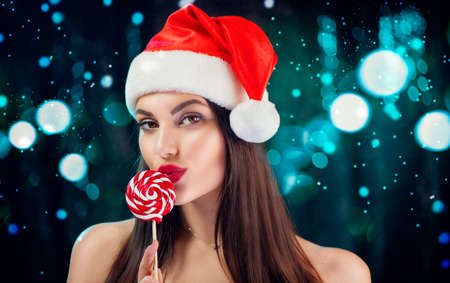 Christmas woman. Beauty model girl in Santa Claus hat with red lips and xmas lollipop candy in her hand. Joy. Surprised expression. Closeup portrait over winter glowing background