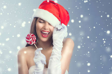 Christmas woman. Beauty model girl in Santa Claus hat with red lips and xmas lollipop candy in her hand. Joy. Surprised expression. Closeup portrait over winter snow background