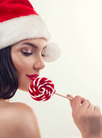 Christmas woman. Beauty model girl in Santa Claus hat eating red xmas lollipop candy. Closeup portrait on grey background. New Year party, celebrating