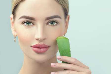 Skin care. Beauty Woman with perfect skin holding fresh leaf of Aloe Vera. Portrait of Beautiful Blonde Spa Girl with perfect healthy skin. Skincare, moisturizing. Proposing a skin care product Standard-Bild