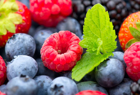 Berries. Various colorful berries background. Mint leaves, Strawberry, Raspberry, Blackberry, Blueberry close-up backdrop. Fresh Bio Fruits, Healthy eating, diet, dieting concept, organic food