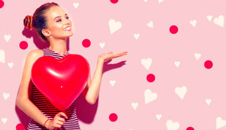 Valentine Beauty girl with red heart shaped air balloon pointing hand. Beautiful Happy Young woman presenting products. Holiday party, birthday. Love concept. Valentines's Day celebrating Standard-Bild