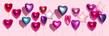 Air Balloons. Bunch of colorful purple, pink, blue heart shaped foil balloons on pink background. Love. Holiday celebration. Valentine's Day party decoration. Birthday. Metallic balloon. Wide screen.