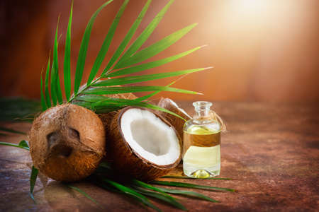Coconut palm oil in a bottle with coconuts and green palm tree leaf on brown background. Coco nut closeup. Healthy Food, skin care concept. Vegan food. Skincare treatments. Aromatherapy. Standard-Bild