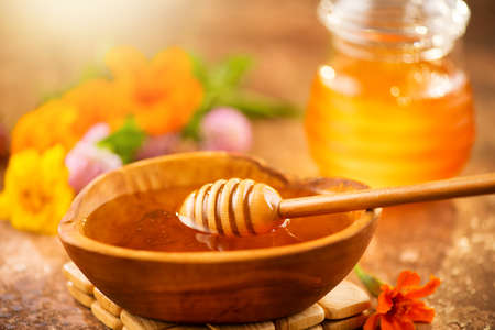Honey dripping from honey dipper in wooden bowl. Close-up. Healthy organic Thick honey dipping from the wooden honey spoon, closeup. Flowers and jar on the table. Banque d'images