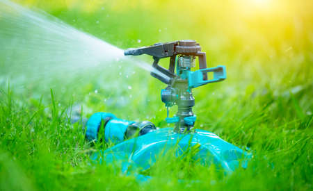 Sprinkler head watering green grass lawn. Gardening concept. Smart garden activated with full automatic sprinkler irrigation system working in a green park. Water Standard-Bild