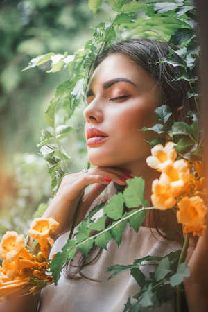 Beautiful young woman posing in Trumpet vine flowers in summer garden. Beauty model girl with Campsis. Enjoying nature outdoor. Standard-Bild