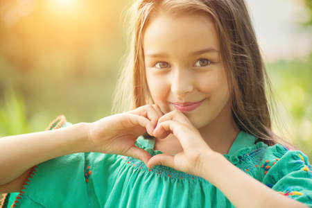 Cute child, little girl showing heart gesture and smiling outdoor. Love summer. Beautiful seven years old child enjoying nature outdoors. Healthy carefree kid playing outside in a park Zdjęcie Seryjne
