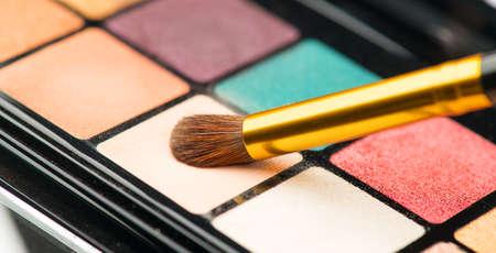 Make up eyeshadows palette set and brush. Professional multicolor eyeshadow. Makeup. Professional multicolor eye shadow make-up palette background, close-up. Colorful bright eye shadows set backdrop.