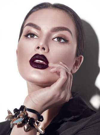 Beauty Fashion model girl with dark lips portrait, wearing stylish woman portrait with perfect makeup, trendy accessories and fashion wear. Beauty trends. Perfect skin. White background Archivio Fotografico