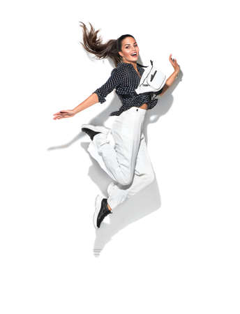 Beauty model girl jumping in trendy fashionable spring clothes, wear, apparel.  Beautiful young brunette woman in trendy outfit, fashion accessories. Isolated on white background. Urban street style