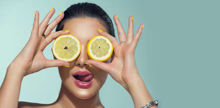 Beautiful healthy girl with slices of lemon citrus fruit, food, cosmetics.