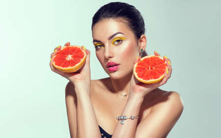 Healthy eating, diet. Beautiful healthy model girl with slices of red grapefruit, food, cosmetics concept.