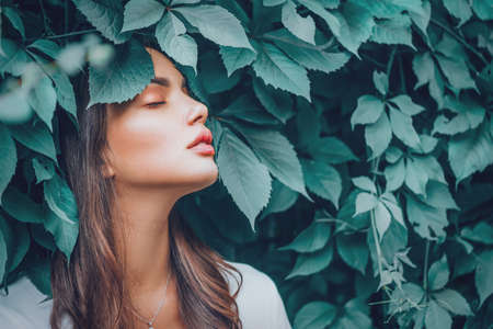 Beautiful fashion model girl enjoying nature, breathing fresh air in summer Stock Photo