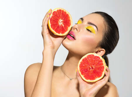 Healthy eating, diet. Beautiful healthy model girl with slices of red grapefruit, food, cosmetics concept. Beauty young fashion woman takes grapefruits, organic vegetables. Vegetarian