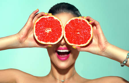 Beauty young fashion woman holding grapefruits, organic vegetables.