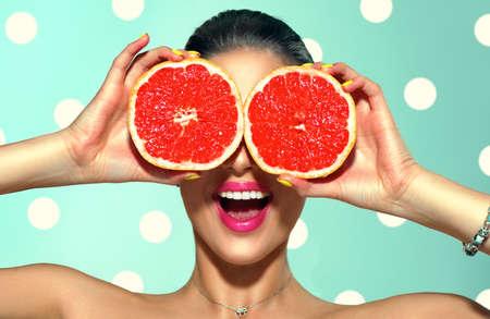 Beauty young fashion woman holding grapefruits, organic vegetables. Vegetarian Stock Photo