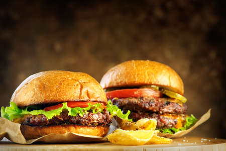 Hamburger and Double Cheeseburger with french fries rotated on wooden table background. Cheeseburgers on fresh buns with succulent beef and fresh salad ingredients served with French Fries. Stock Photo