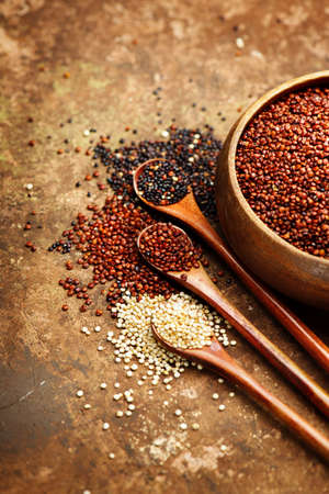 Red, black and white quinoa grains in a wooden spoon. Healthy food in a bowl. Seeds of white, red and black quinoa - Chenopodium quinoa. Diet, Dieting concept. Vegan food. Vertical image