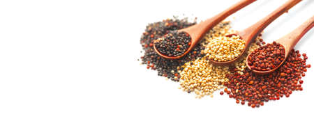 Black, red and white quinoa grains in a wooden spoon isolated on white background. Gluten free Healthy food. Seeds of white, red and black quinoa - Chenopodium quinoa closeup.