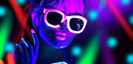 Disco dancer in neon light in night club Fashion model woman in neon light, portrait of beautiful girl with fluorescent make-up, Body Art design in UV, sunglasses, colorful make up. Stock Photo