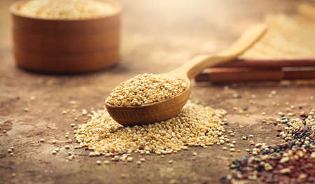 Quinoa White grains in a wooden bowl and spoon. Gluten free Healthy food. Diet, dieting concept. Seeds of white quinoa - Chenopodium quinoa.