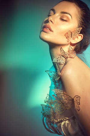 Beauty model girl in colorful bright neon lights posing, fashion make up with butterfly. Portrait of beautiful summer young woman in UV. Art design colorful make up with golden butterflies.