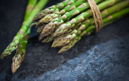 Asparagus. Fresh raw organic green Asparagus sprouts closeup. On black slate table background. Healthy vegetarian food. Raw vegetables, market. Healthy eating concept, diet, dieting