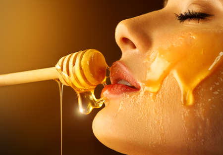 Honey dripping from honey dipper on sexy girl lips. Thick honey dipping from the wooden honey spoon. Beauty model woman open mouth, model eating nectar. Healthy food concept, diet, dessert
