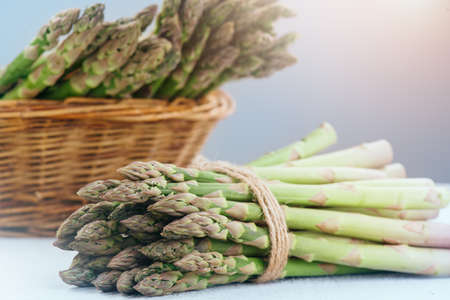 Asparagus. Fresh raw organic green Asparagus sprouts closeup. Basket and bunch n the table. Healthy vegetarian food. Raw vegetables, market. Healthy eating concept, diet, dieting.