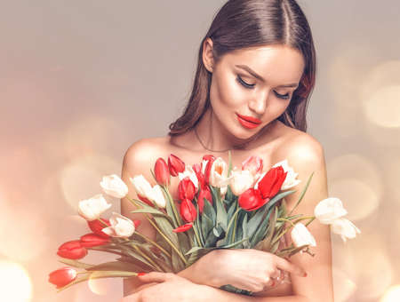 Beauty glamour girl with Spring tulips Flower bouquet. Beautiful young woman with a bunch of colorful Tulip flowers. Happy model posing with summer flowers. Valentine's Day. Birthday party. Gift Stock Photo