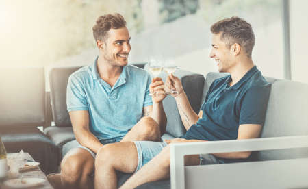 Two young men sitting on the sofa, talking and drinking wine after dinner together. Gay couple dating at home or in a restaurant, flirting and smiling.