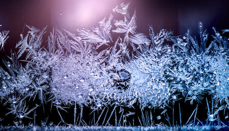 Frozen winter window. Window frozen glass, ice crystals. Snow frame. Beautiful Hoarfrost pattern, rime on black background. Christmas or New Year backdrop. Stock Photo