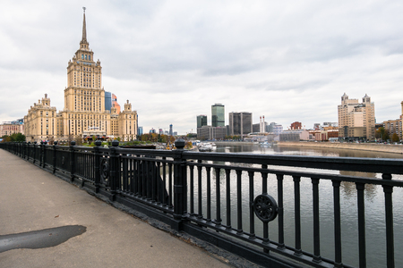 MOSCOW, RUSSIA. OCTOBER,24.2017: Elegant iron wrought fence of the Novoarbatskiy bridge. Famous skyscraper of the former Soviet hotel `Ukraine`.