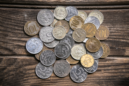 Bunch of coins on the aged wooden surface. Russian roubles. Miserable poverty. Rural dreams of wealth. The concept of social inequality. Stock Photo