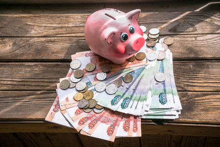 A ray of sunlight on the funny piggy bank and bunch of banknotes and coins on the aged rough wooden windowsill. Stock Photo