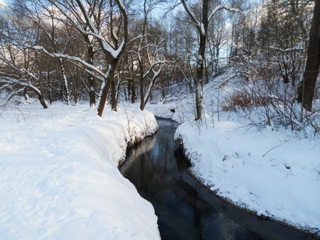 Nonfreezing Ramenka river on a tranquil clear winter day. Moscow. Russia. Fluffy snow adorns leafless trees with festive dresses. Winter nature delights eyes with blinding purity. Фото со стока