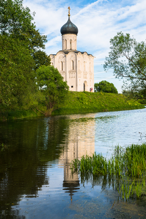Pristine riverside landscape next to of the Russian ancient shrine is full of serenity. Orthodox Church of the Intercession on the Nerl River