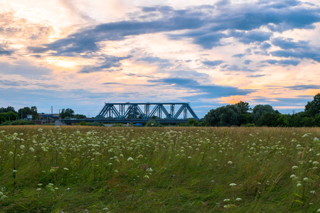 Evening sky over the railway bridge and flowered Bogolyubovo meadow, Vladimir region.