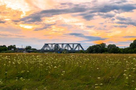 Evening sky over the railway bridge and flowered Bogolyubovo meadow, Vladimir region. Stock fotó - 108880073