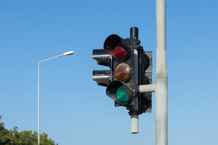 lamp post: traffic light against a clear blue sky, with lamp post in background